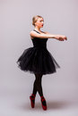 Young blonde ballerina girl dance and posing in black tutu and ballet shoes on grey background Royalty Free Stock Photo