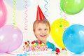 Young blonde boy in festive hat with birthday cake and balloons Royalty Free Stock Photo