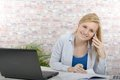 Young blonde businesswoman using her phone in her office Royalty Free Stock Photo