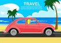 Young blonde driving retro car along the sea coast