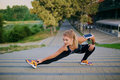 Young blonde girl doing warm-up in the park on autumn. Royalty Free Stock Photo