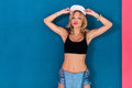 Young blonde girl posing wearing urban clothes sports bra swag baseball cap or hat Royalty Free Stock Photo