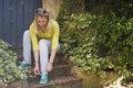 Young blonde girl ties up shoelaces on sneakers Royalty Free Stock Photo