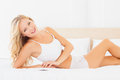 Young blonde lying on bed smiling at camera home in the bedroom Royalty Free Stock Photography