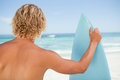 A young blonde man holding a perched surfboard Royalty Free Stock Photography