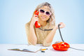 A young blonde at table with telephone the Royalty Free Stock Image