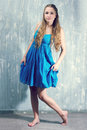Young blonde woman in blue dress Stock Photo