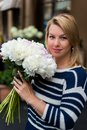 Young blonde woman in blue dress with peonies bouquet Royalty Free Stock Photo