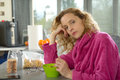 Young blonde woman eating cereals in the morning Royalty Free Stock Photo