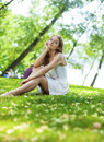 Young blonde woman on green meadow sexy in white dress sitting grass in summer park Royalty Free Stock Photography