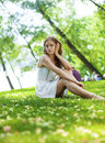 Young blonde woman on green meadow sexy in white dress sitting grass in summer park Stock Photography