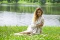 Young blonde woman on green meadow sexy in white dress sitting grass in summer park Royalty Free Stock Photos