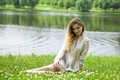 Young blonde woman on green meadow sexy in white dress sitting grass in summer park Stock Photos
