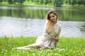 Young blonde woman on green meadow sexy in white dress sitting grass in summer park Royalty Free Stock Photo