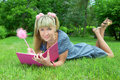 Young blonde woman reading book in park Stock Photography