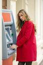 Young blonde woman in a red coat withdraw cash from an atm in th shopping center Stock Photo
