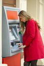 Young blonde woman in a red coat withdraw cash from an atm in th shopping center Royalty Free Stock Photography