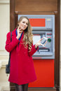 Young blonde woman in a red coat withdraw cash from an atm in th shopping center Royalty Free Stock Image