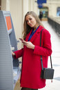 Young blonde woman in a red coat withdraw cash from an atm in th shopping center Stock Photography