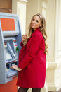 Young blonde woman in a red coat withdraw cash from an atm in th shopping center Stock Image