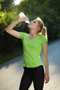 Young blonde woman runner holds blue bottle Stock Photography