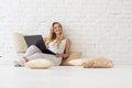 Young Blonde Woman Sit On Floor  Pillows Using Laptop Computer, Beautiful Girl Happy Smiling Look Up To Copy Space Royalty Free Stock Photo