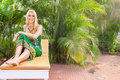Young blonde woman at tropical resort in front of palm tree Royalty Free Stock Image