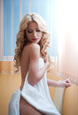 Young blonde woman wrapped in white towel posing relaxed. Beautiful young woman with a towel around her body after bath. Side view Royalty Free Stock Photo