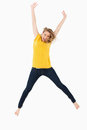 Young blonde woman in yellow shirt jumping Royalty Free Stock Image