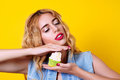 Young blondy model is enjoyment with delicious cupcake over yellow background.