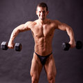 Young bodybuilder traininig over balck background Stock Photos