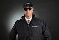 Young bodyguard in uniform portrait of wearing sunglasses over black background Royalty Free Stock Photos
