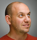 Young bold man portrait of an happy bald against gray background Royalty Free Stock Photography