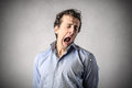 Young bored man yawning with a very expression Royalty Free Stock Photos