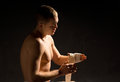 Young boxer psyching himself up in the darkness before a fight sitting wrapping his knuckles a bandage Royalty Free Stock Image