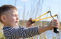 Young Boy Aiming Sling Shot Over Lake Royalty Free Stock Photo