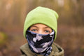 Young boy in bandanna wearing a hat and covering his face Royalty Free Stock Photo