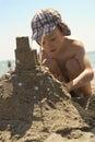 Mladý chlapec na pláž tvorba hrad z piesku