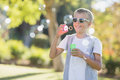 Young boy blowing bubbles through bubble wand Royalty Free Stock Photo