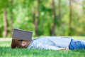Young boy with a book slipping on green grass in the park Royalty Free Stock Images