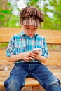 Young boy browsing internet browses on his phone Royalty Free Stock Image