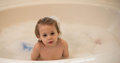 Young boy in a bubble bath enjoys at home Stock Photo