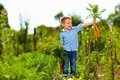 Young boy with carrot enjoying life in countryside fresh Royalty Free Stock Photos