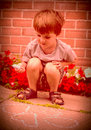 Young boy chalk drawing abstract crouched down and hearts on the sidewalk with Royalty Free Stock Image