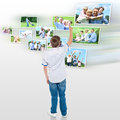 Young boy choosing his outdoor photo to share rear view of looking pictures in virtual screen Royalty Free Stock Image