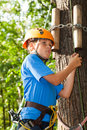 Young boy climber equipment intently keeps rope Stock Image