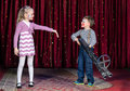 Young Boy Clown Aiming Large Gun at Blond Girl Royalty Free Stock Photo