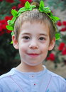 Young boy with a crown of leaves wearing vine prepared traditionally to celebrate the jewish festival shavuot feast weeks or Royalty Free Stock Image