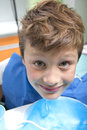 Young boy in a dental surgery drinking water after operation Stock Photo