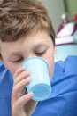Young boy at the dentist drinking water after dental operation Royalty Free Stock Photo